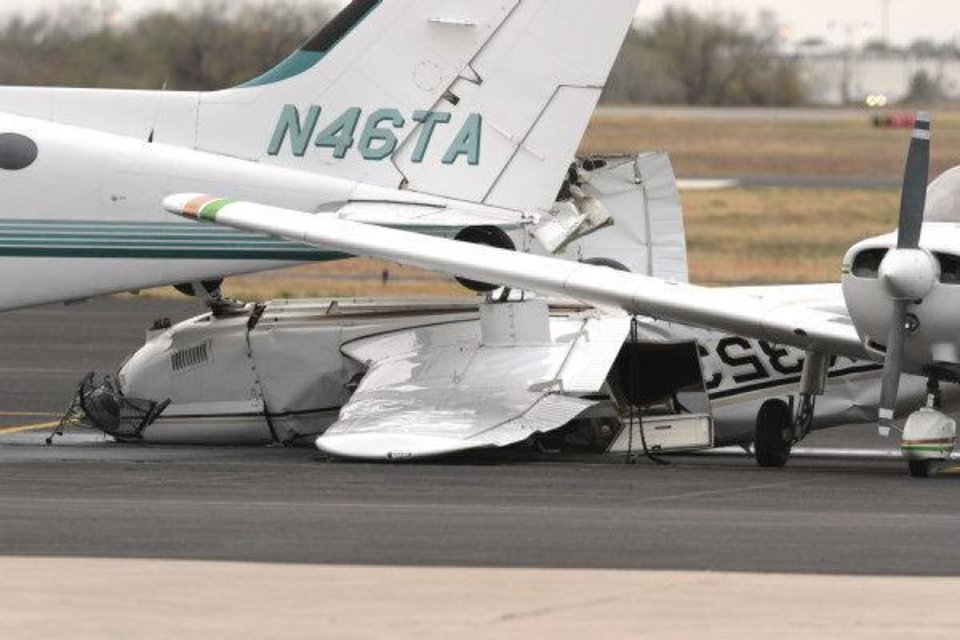 Photo - A crumpled airplane on the tarmac shows damage from Monday nights severe weather at Max Westheimer Airport on Tuesday, Nov. 8, 2011, in Norman, Okla. Photo by Steve Sisney, The Oklahoman ORG XMIT: KOD