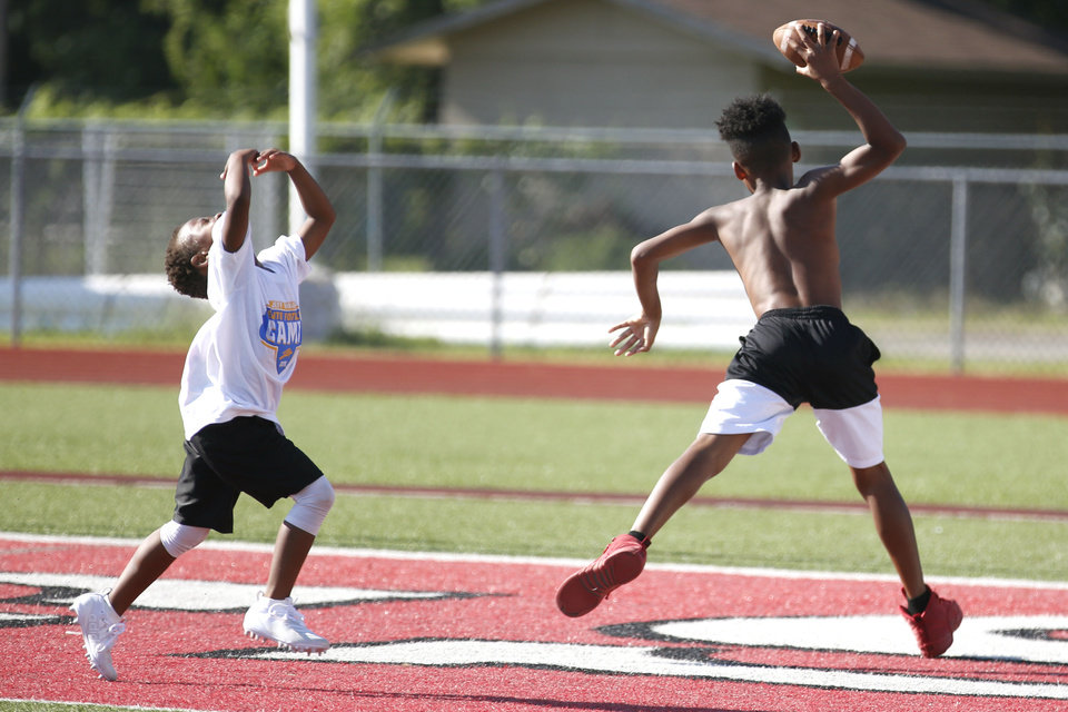 Photo - A camp participant spikes the ball after making it into the end zone at Los Angeles Chargers player Jeff Richards Elite Football Camp at Del City High School in Del City, Oklahoma on July 13, 2019. [Paxson Haws/The Oklahoman]