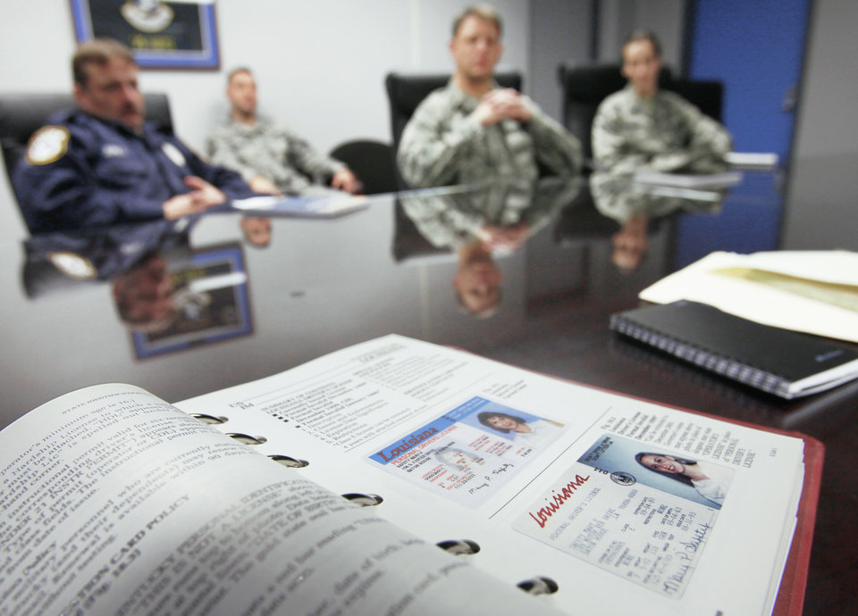 Vance Air Force Base officials discussed security at the base after disclosure that some undocumented immigrants had made it onto the base to work. In the foreground is a book used to help spot fake IDs.  PHOTO BY David McDaniel, The Oklahoman