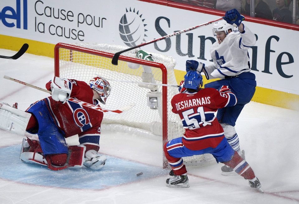 Photo - Montreal Canadiens goaltender Carey Price, left, is scored on by Toronto Maple Leafs' Korbinian Holzer, right, as Canadiens' David Desharnais defends during the third period of an NHL hockey game in Montreal, Saturday, Feb. 9, 2013. (AP Photo/The Canadian Press, Graham Hughes)