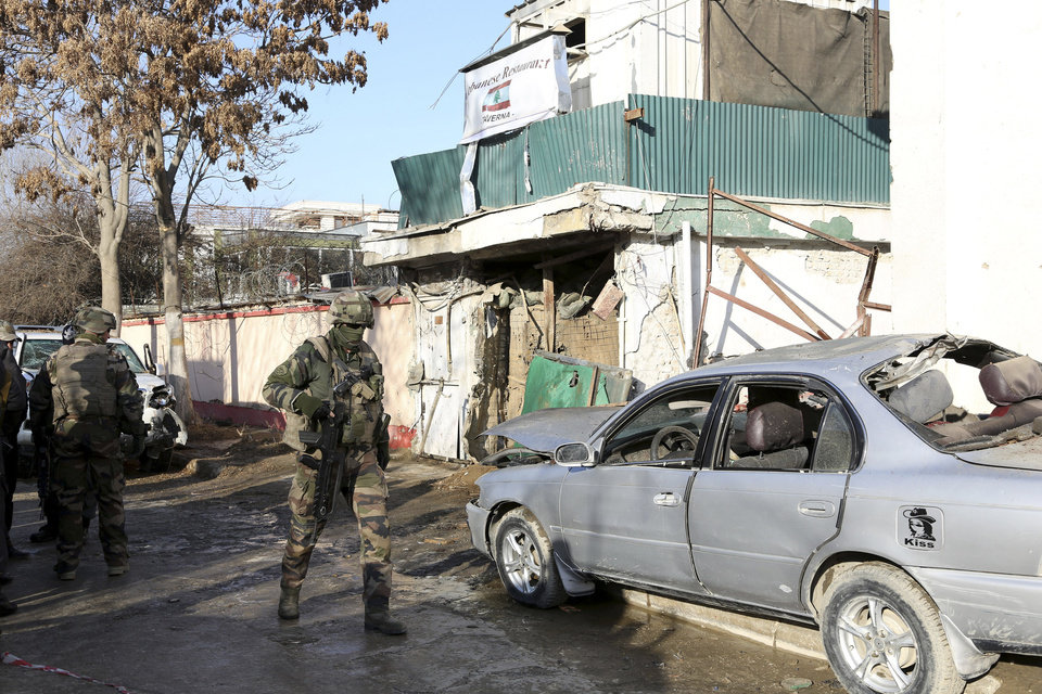 NATO International security assistance forces personnel investigate at the site of the Friday's suicide attack and shooting, in Kabul, Afghanistan, Saturday, Jan. 18, 2014. A Taliban suicide bomber and two gunmen on Friday attacked a Lebanese restaurant that is popular with foreigners and affluent Afghans in Kabul, a brazen attack that left 16 dead, including foreigners dining inside and two other gunmen, officials said. (AP Photo/Rahmat Gul)