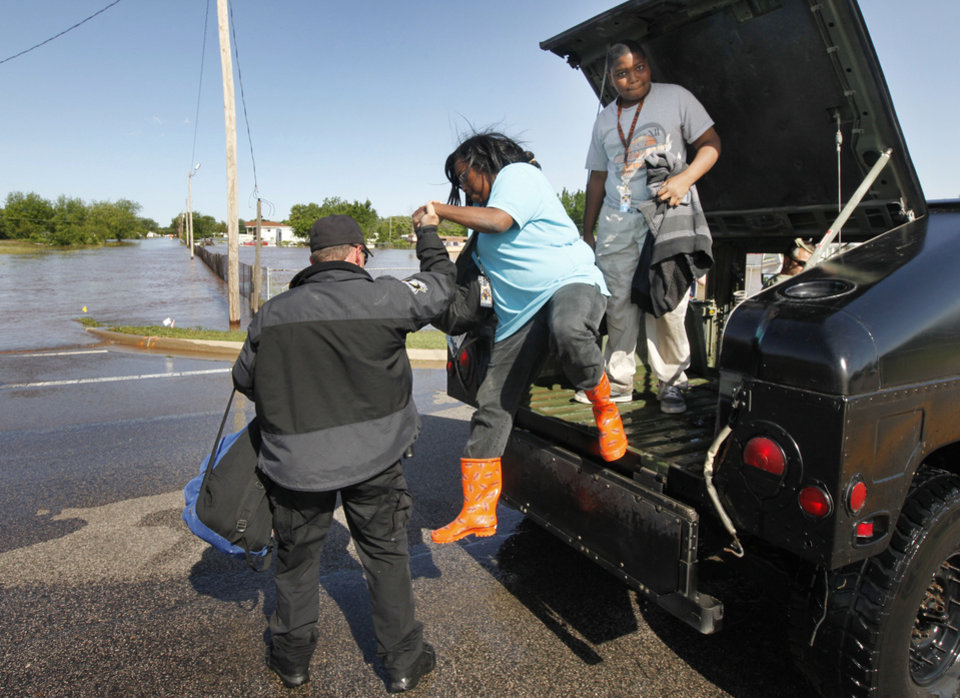 Erica Freeman and Eysaih Jennings step down from an Oklahoma County Sheriff's Dept. Humvee after being rescued from a flooded mobile home park off of Air Depot Blvd. between NE 10th and NE 23rd St. in Midwest City, OK, Saturday, June 1, 2013, after up to eight inches of rain fell during the previous 24 hours. Photo by Paul Hellstern, The Oklahoman