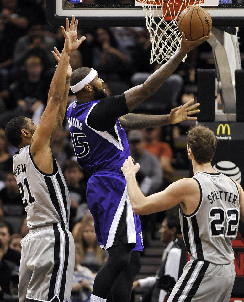 Photo - Sacramento Kings center DeMarcus Cousins, center, shoots against San Antonio Spurs forwards Tiago Splitter, right, of Brazil, and Tim Duncan, during the first half of an NBA basketball game on Sunday, Dec. 29, 2013, in San Antonio. (AP Photo/Darren Abate)