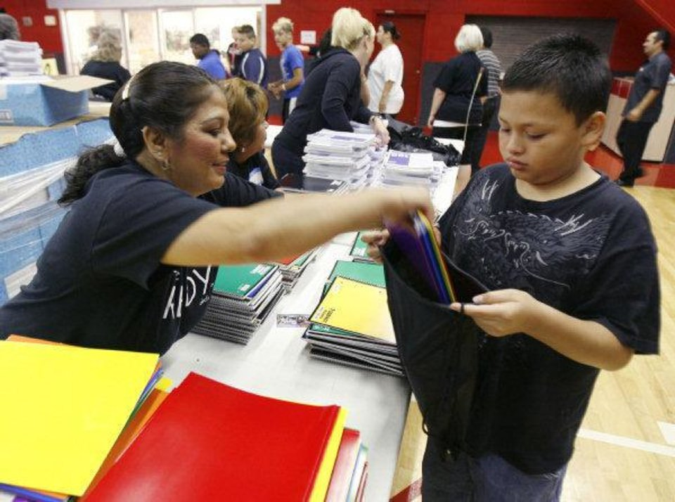 Photo - Church member Deborah Humphrey places folders in the backpack of Bryan Cifuentes, 10, during the 2009 Feeding the 5,000 back-to-school event at OKC Faith Church in Oklahoma City. Oklahoma Archive photo by Paul Hellstern  PAUL HELLSTERN