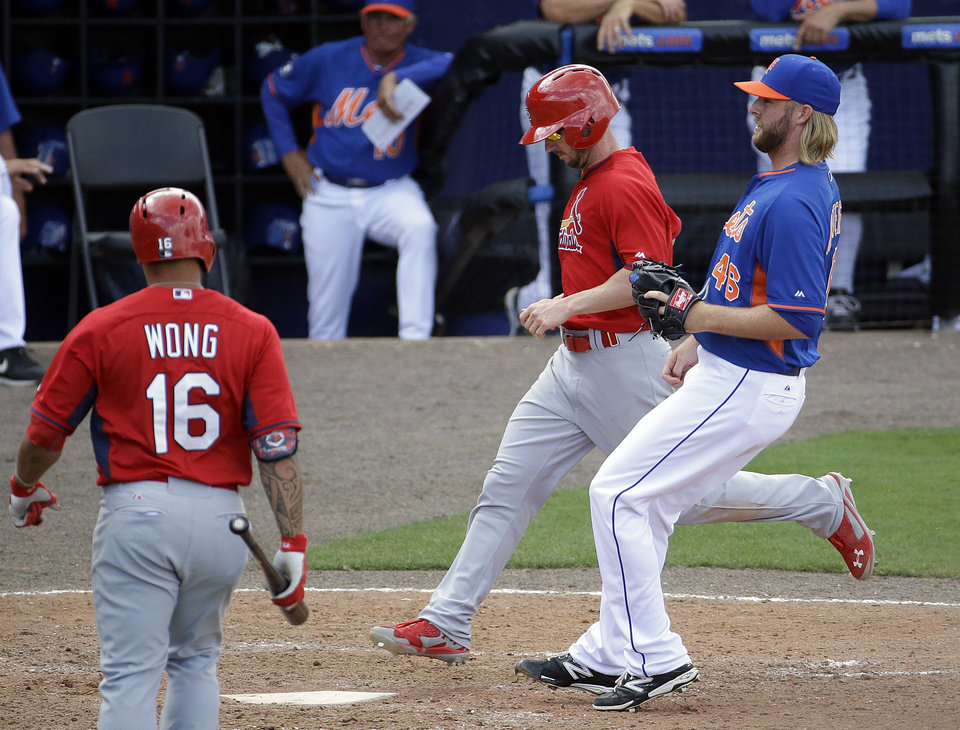 Photo - St. Louis Cardinals' Shane Robinson, second from right, scores on a wild pitch by New York Mets' Jeff Walters, right, in the eighth inning of an exhibition spring training baseball game, Wednesday, March 12, 2014, in Port St. Lucie, Fla. (AP Photo/David Goldman)