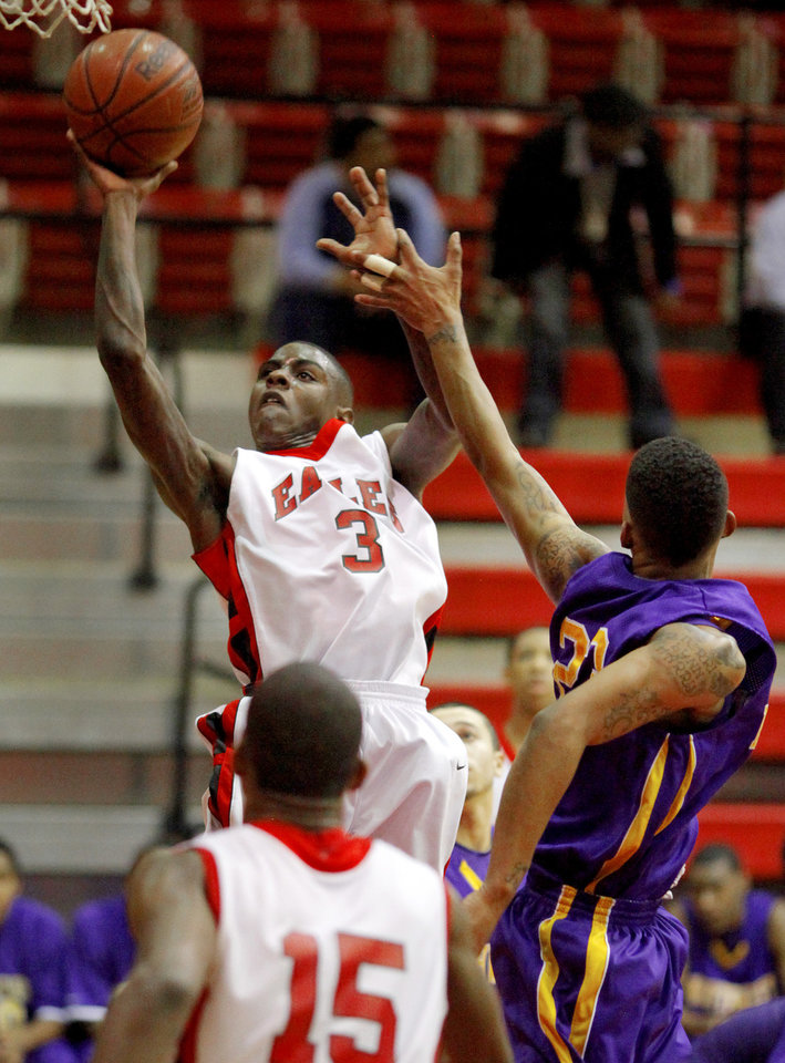 Del City's Anthony Holland puts up a shot beside Northwest Classen's Trell Harris during the boys Class 5A regional basketball game in Del City, Okla., Saturday, Feb. 25, 2012. Photo By Bryan Terry, The Oklahoman