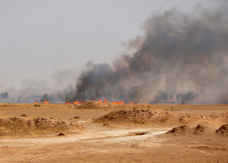 Photo - In this photo taken on Saturday, June 28, 2014, smoke rises during a military operation to regain control of Dallah Abbas north of Baqouba, the capital of Iraq's Diyala province, 35 miles (60 kilometers) northeast of Baghdad, Iraq. Islamic State in Iraq and the Levant which already controls vast swaths in northern and eastern Syria amid the chaos of that nation's civil war, aims to erase the borders of the modern Middle East and impose its strict brand of Shariah law. (AP Photo)