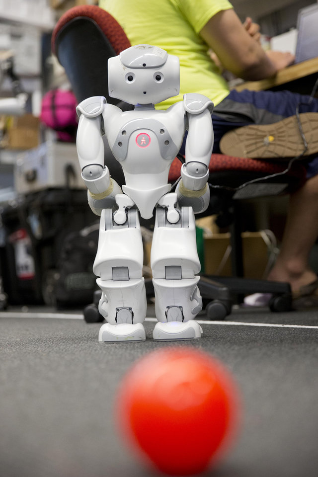 Photo - In this July 7, 2014, photo, students at the University of Pennsylvania work with one of their RoboCup entries the school in Philadelphia. The idea is to program robots to make quick, smart decisions while working together in a changing environment. (AP Photo/Matt Rourke)