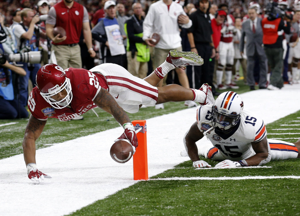 Photo - Oklahoma's Joe Mixon (25) scores a touchdown over Auburn's Joshua Holsey (15) in the third quarter during the Allstate Sugar Bowl between University of Oklahoma Sooners (OU) and Auburn University Tigers at the Mercedes-Benz Superdome in New Orleans, Monday, Jan. 2, 2017.  Photo by Sarah Phipps, The Oklahoman