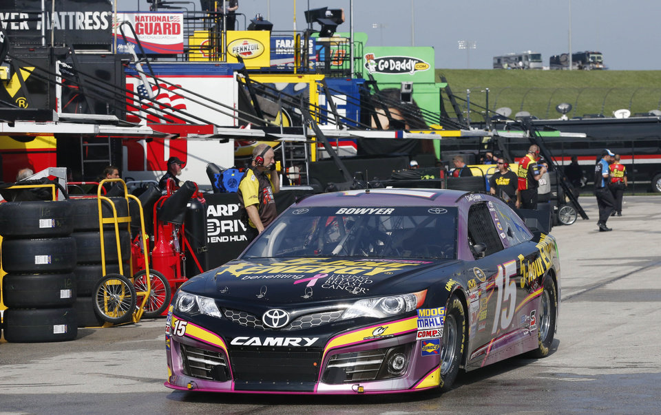 Photo - NASCAR Sprint Cup Series driver Clint Bowyer (15) drives through the garage area at Kansas Speedway in Kansas City, Kan., Thursday, Oct. 3, 2013. NASCAR auto racing teams are testing tires at the recently re-surfaced speedway. (AP Photo/Orlin Wagner)
