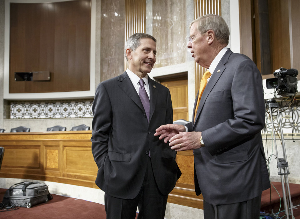 Photo - Veterans Affairs acting Secretary Sloan Gibson, left, talks with  Sen. Johnny Isakson, R-Ga., on Capitol Hill in Washington, Wednesday, July 16, 2014, prior to testifying before the Senate Veterans' Affairs Committee hearing on the state of VA health care in the wake of revelations of neglect and delayed medical visits.   (AP Photo/J. Scott Applewhite)
