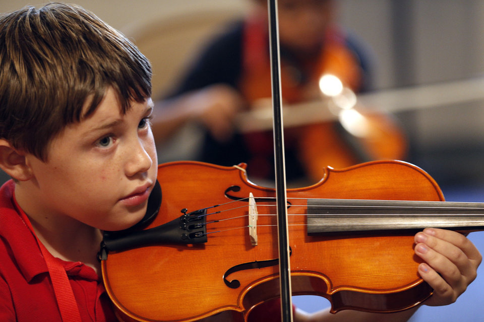Photo - Elliott Miller plays the violin during a session of El Sistema Oklahoma, a new after-school program being sponsored by St. Luke's United Methodist Church, Oklahoma City University and the Foundation for Oklahoma City Public Schools.   SARAH PHIPPS - SARAH PHIPPS