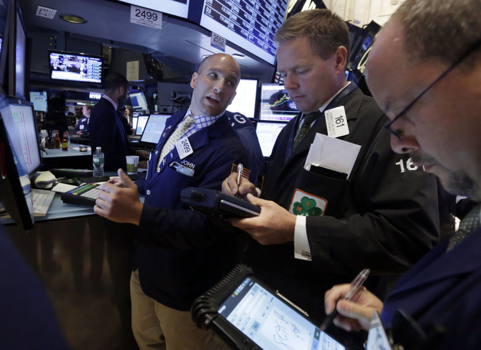 Photo - Specialist John Parisi, left, works with traders on the floor of the New York Stock Exchange Wednesday, July 9, 2014.  Stocks inched higher in early trading Wednesday, reversing a two-day decline, as the quarterly earnings season got underway with some positive news from the giant aluminum company Alcoa. (AP Photo/Richard Drew)
