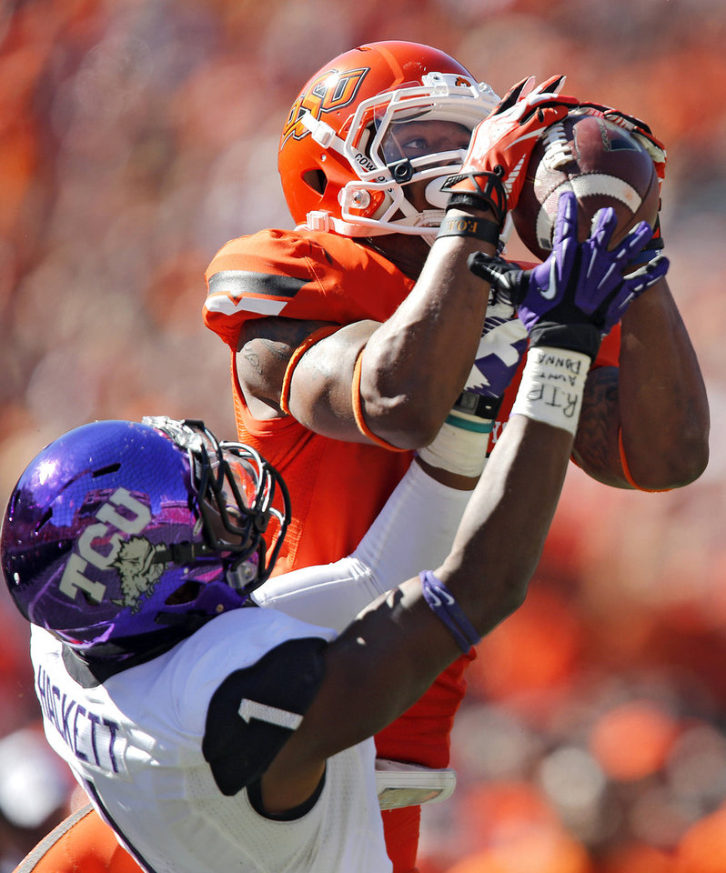 Oklahoma State�s Josh Stewart makes a catch over TCU�s Chris Hackett. Photo by Chris Landsberger, The Oklahoman