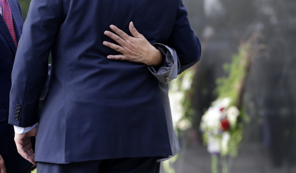 Photo - The hand of Belva Pichon, president of Crescent City Funeral Directors and Embalmers Association, hugs New Orleans Mayor Mitch Landrieu during a wreath-laying ceremony at the Hurricane Katrina Memorial, on the ninth anniversary of the storm, in New Orleans, Friday, Aug. 29, 2014. Behind is an unmarked mausoleum, which contains unidentified bodies of people who died in the storm. (AP Photo/Gerald Herbert)