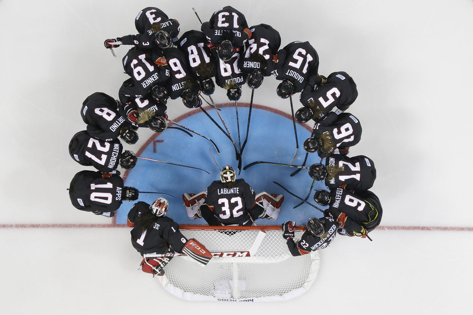 Photo - Team Canada huddles before their women's ice hockey game at the Shayba Arena against Switzerland during the 2014 Winter Olympics, Saturday, Feb. 8, 2014, in Sochi, Russia. (AP Photo/Matt Slocum )