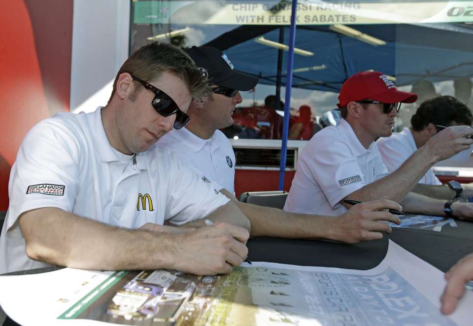 Photo - Ganassi Racing team drivers from left, Jamie McMurray, Joey Hand and Scott Dixon, of New Zealand, sign autographs for fans prior to the start of the Grand-Am Series Rolex 24 hour auto race at Daytona International Speedway, Saturday, Jan. 26, 2013, in Daytona Beach, Fla. (AP Photo/John Raoux)