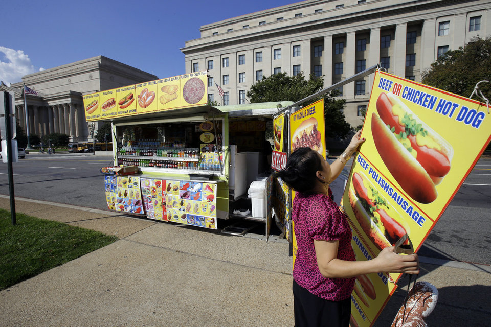Photo - Cathy Vu, from Annandale, Va., packs up her truck on Constitution Avenue across the street from the National Archives, behind left, and Federal Trade Commission (FTC) behind right, Friday, Oct. 4, 2013, in Washington. Vu said today is the only day this week she has come out with the truck, and that business has been bad, since the federal government shutdown started Tuesday.  (AP Photo/Alex Brandon)