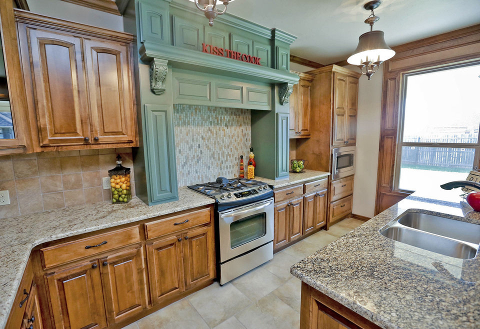 Photo - Granite counters and custom maple cabinetry are featured in the kitchen of the House of Hope by Raywood Homes in Yukon.  CHRIS LANDSBERGER - The Oklahoman