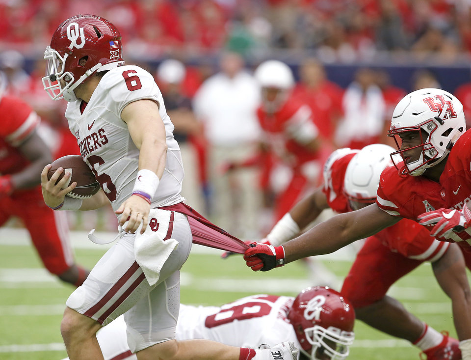 Photo - Oklahoma's Baker Mayfield (6) tries to get past Houston's Houston's Ed Oliver (10) during the AdvoCare Texas Kickoff college football game between the University of Oklahoma Sooners (OU) and the Houston Cougars at NRG Stadium in Houston, Saturday, Sept. 3, 2016. Houston won 33-23. Photo by Bryan Terry, The Oklahoman