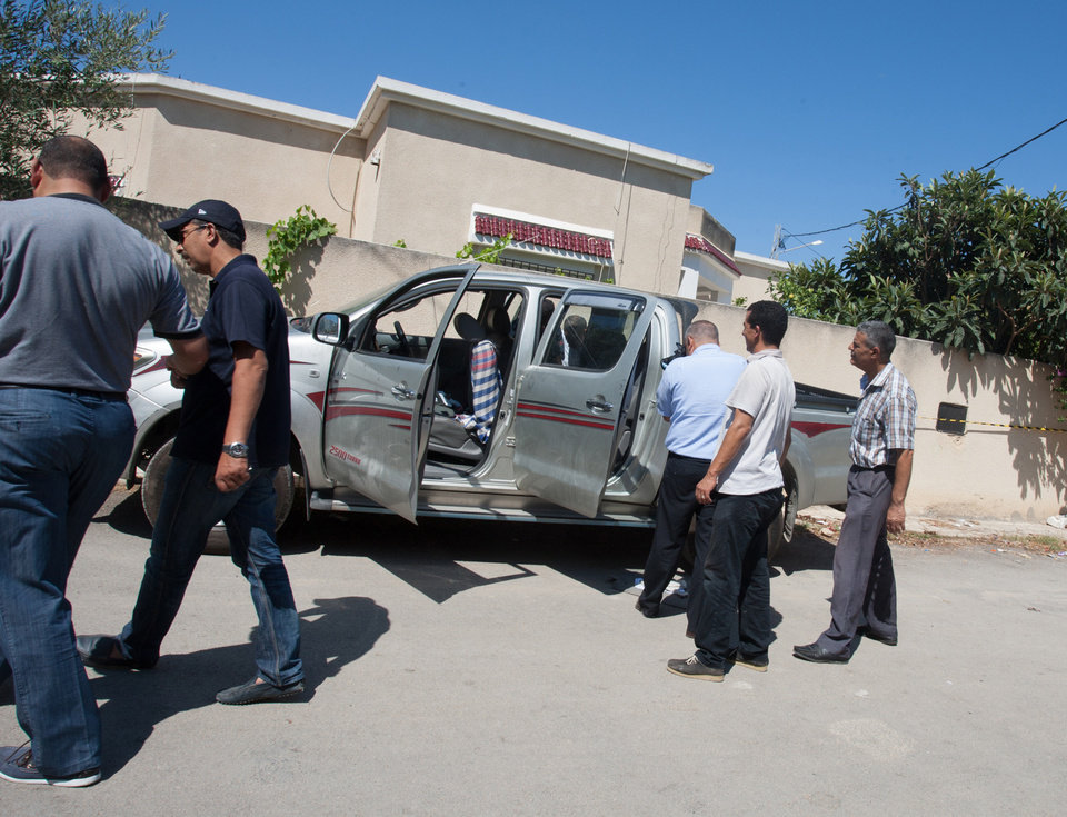 Photo - Tunisian police officers inspect Mohammed Brahmi's car in which he was shot to death outside his home in Tunis, Tunisia, Thursday, July 25, 2013. Brahmi, 58, of an Arab nationalist political party was in his car  when gunmen fired several shots at him, said Interior Ministry spokesman Mohammed Ali Aroui. It is the second killing of an opposition member this year, following that of Chokri Belaid, a member of the same leftist Popular Front coalition as Brahmi. Belaid was also shot dead in his car outside his home in February. His killing provoked a political crisis that nearly derailed Tunisia's political transition. (AP Photo/Amine Landoulsi)