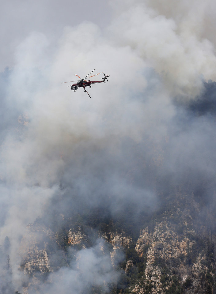 Photo - A Heavy Type-1 Skycrane Helictoper flies over the Slide Fire before dumping a 2,000 gallon load of water as it burns up Oak Creek Canyon on Friday, May 23, 2014, near Flagstaff, Ariz.  The fire has burned approximately 7,500 acres and is five percent contained. (AP Photo/Ross D. Franklin)