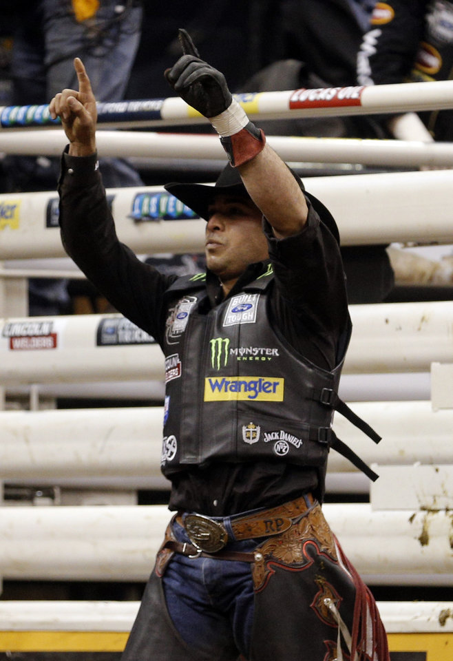 Photo - Robson Palermo celebrates his ride on  Rock & Roll during the Express Employment Professionals Invitational PBR  event at the Chesapeake Energy Arena in Oklahoma City, SUnday, Jan. 26, 2014.  Photo by Sarah Phipps, The Oklahoman