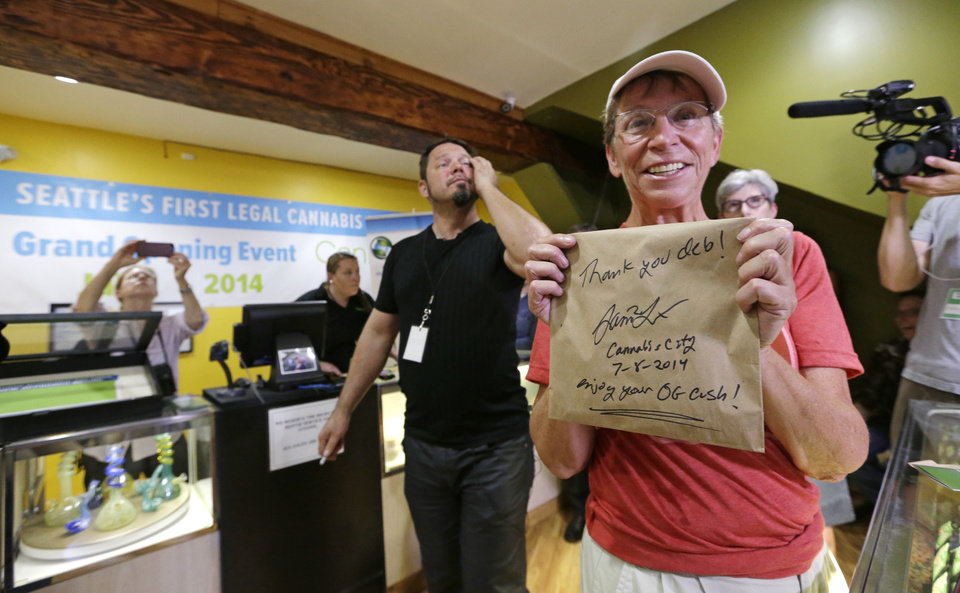 Photo - Deb Greene, the store's first customer, displays her purchase of legal recreational marijuana at Cannabis City as owner James Lathrop walks past Tuesday, July 8, 2014, in Seattle. Greene was the first customer, having waited in line since Monday afternoon. Washington on Tuesday became the second state to allow people to buy marijuana legally in the U.S. without a doctor's note as eager customers who lined up outside stores made their purchases and savored the moment. (AP Photo/Elaine Thompson, Pool)