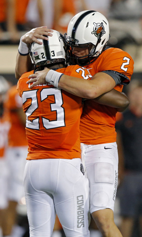 Photo - Oklahoma State's Mason Rudolph (2) and Rennie Childs (23) hug after the 45-38 win over Pittsburg during a college football game between the Oklahoma State Cowboys (OSU) and the Pitt Panthers at Boone Pickens Stadium in Stillwater, Okla., Saturday, Sept. 17, 2016. Photo by Chris Landsberger, The Oklahoman