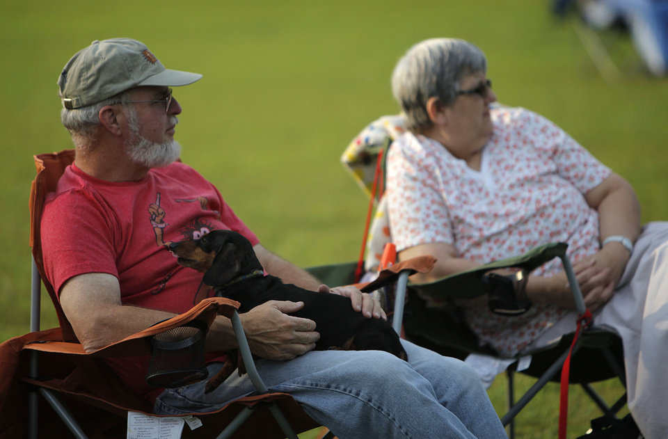 Photo - Eddie Schriewer sits with his dog, Greta,  as he and his wife, Bonnie, watch Doc Blues Revue band perform during the Midwest Twilight Concert in Midwest City on Thursday.  Garett Fisbeck - THE OKLAHOMAN