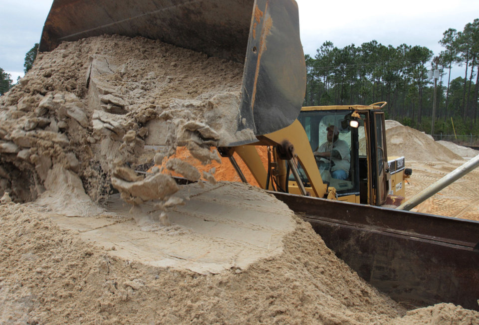 Photo - Tony Buckley of Vancleave, Miss., loads sand into a truck at the Jackson County Road Department barn in Vancleave on Monday Jan. 27, 2014. The sand will be spread on bridges if they ice over during an expected wonter storm on Tuesday and Wednesday. (AP Photo/Sun Herald, John Fitzhugh)