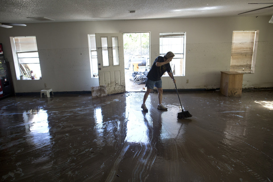 Photo - Diana Ward helps clean up the First Independent Baptist Church after heavy rains caused water levels to rise over four feet in the church before receding on Thursday Oct. 31, 2013 in Austin, Texas. The National Weather Service said more than a foot of rain fell in Central Texas. (AP Photo/ Tamir Kalifa)