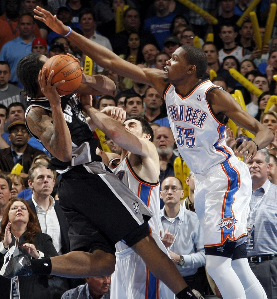 Oklahoma City's Kevin Durant (35) and Nick Collison (4) defend San Antonio's Kawhi Leonard (2) during the NBA basketball game between the Oklahoma City Thunder and the San Antonio Spurs at Chesapeake Energy Arena in Oklahoma City, Friday, March 16, 2012. San Antonio won, 114-105. Photo by Nate Billings, The Oklahoman