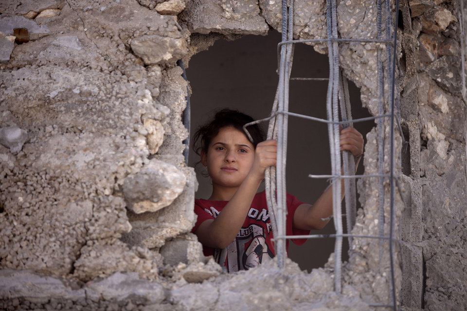 Photo - Mai Awad looks out from the damaged family home of Palestinian Ziad Awad in the town of Idna,13 kilometers (8 miles) west of the West Bank city of Hebron, Wednesday, July 2, 2014. Israel demolished on Wednesday the West Bank home of Ziad Awad, who it accuses of having killed an Israeli police officer in April. The move marks a return to a policy abandoned by the military in 2005. Israel sees house demolitions as a deterrent to violence while critics charge it is a form of collective punishment. (AP Photo/Majdi Mohammed)