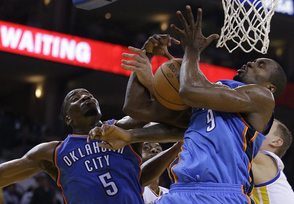 Oklahoma City Thunder's Kendrick Perkins (5) and Serge Ibaka (9) fight for a rebound during the second half of an NBA basketball game against the Golden State Warriors Wednesday, Jan. 23, 2013, in Oakland, Calif. (AP Photo/Ben Margot) ORG XMIT: OAS111
