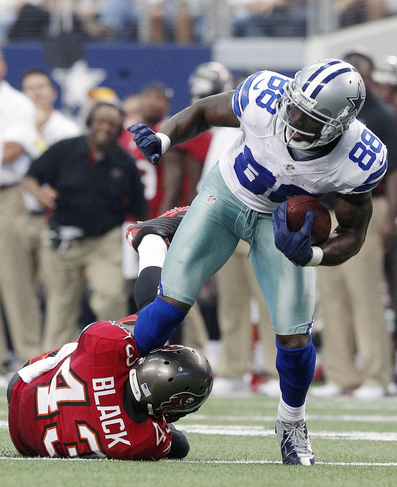 Dallas Cowboys wide receiver Dez Bryant (88) is tackled by Tampa Bay Buccaneers free safety Ahmad Black (43) during the second half of an NFL football game on Sunday, Sept. 23, 2012, in Arlington, Texas. (AP Photo/Tim Sharp)