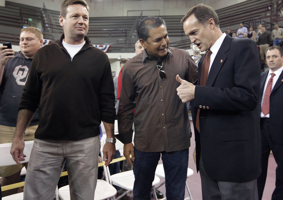 New University of Oklahoma men's basketball coach, right, talks with OU baseball coach Sunny Golloway and football coach Bob Stoops before being introduced as the new University of Oklahoma men's basketball coach on Monday, April 4, 2011, in Norman, Okla.