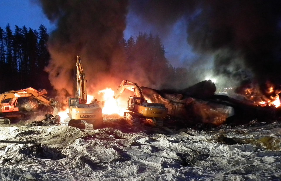Photo - In this Feb. 16, 2015 photo provided by the Transportation Safety Board of Canada, workers fight a fire after a crude oil train derailment south of south of Timmins, Ontario.  As investigators in West Virginia and Ontario pick through the wreckage from the latest pair of oil train derailments to result in massive fires, U.S. transportation officials predict many more catastrophic wrecks involving flammable fuels in coming years absent new regulations. (AP Photo/Transportation Safety Board of Canada)