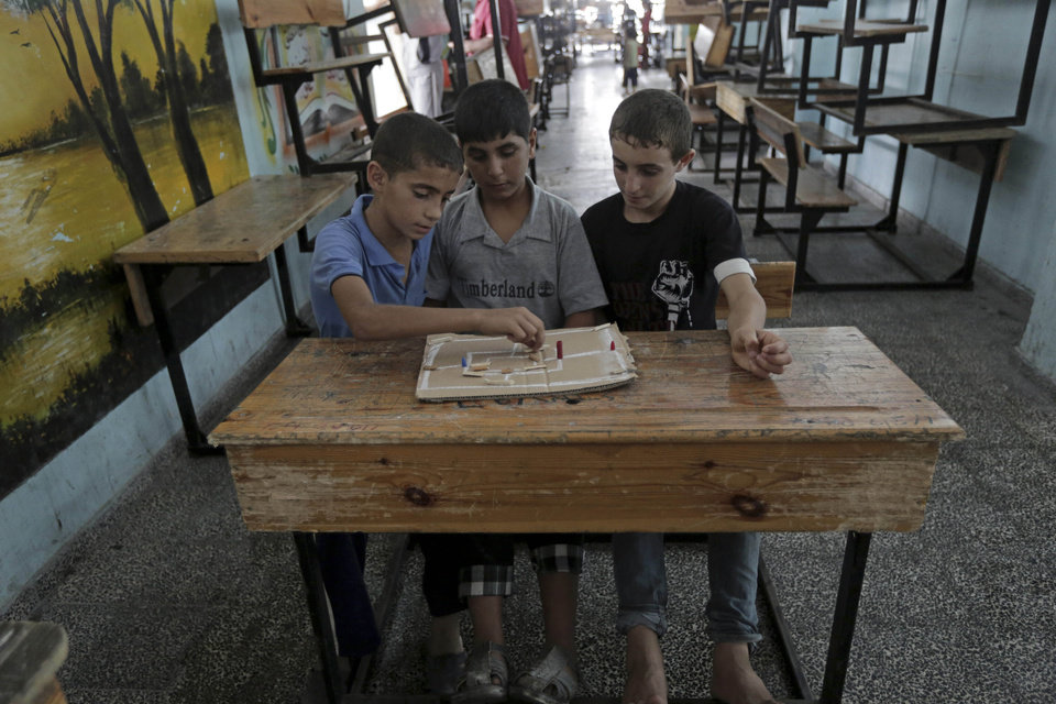 Photo - Palestinian youths play on a school desk after they fled their homes with their family to take shelter at the United Nations school in Gaza City, Sunday, July 13, 2014. Israel briefly deployed ground troops inside the Gaza Strip for the first time early Sunday as its military warned northern Gaza residents to evacuate their homes, part of a widening offensive that has killed more than 160 Palestinians. (AP Photo/Adel Hana)