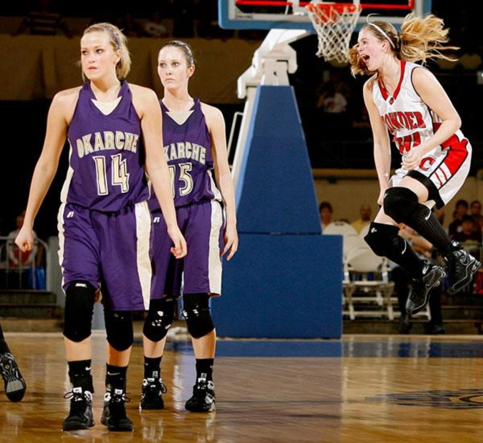 Photo -  Hillary Konsure of Crowder celbrates beside Okarche's Macy Kunneman, left, and Katie Beebe after Crowder's win in the Class A girls basketball state tournament semifinal game at the State Fair Arena in Oklahoma City, Friday, March 6, 2009. PHOTO BY BRYAN TERRY, THE OKLAHOMAN