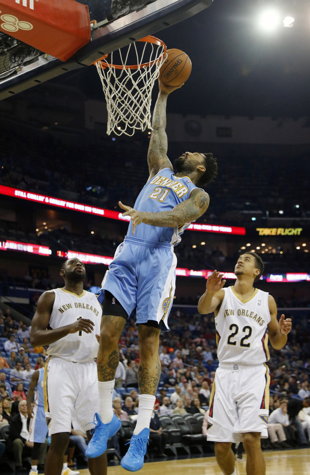 Photo - Denver Nuggets small forward Wilson Chandler (21) goes to the basket as New Orleans Pelicans small forward Tyreke Evans (1) and point guard Brian Roberts (22) watch in the first half of an NBA basketball game in New Orleans, Sunday, March 9, 2014. (AP Photo/Bill Haber)