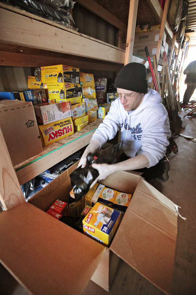 Photo - Members of the Memorial Baptist Church in Fond du Lac, Wis.,  came to McLoud to help at the food pantry at the Emmanuel Baptist Church. Pastor Brian Hastings sorts some supplies in a storage building on Wednesday.  David McDaniel - The Oklahoman