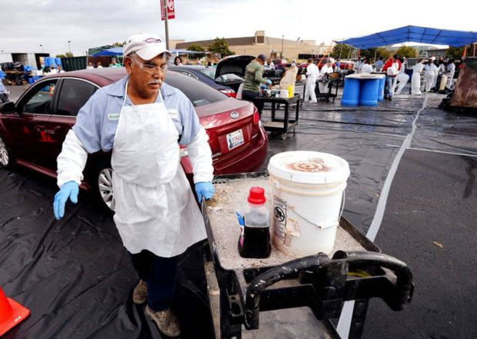 Photo -  Roberto Garcia wears protective gear and gathers materials during a November 2016 hazardous waste collection event in the parking lot of the Lloyd Noble Center. [PHOTO BY STEVE SISNEY, THE OKLAHOMAN]