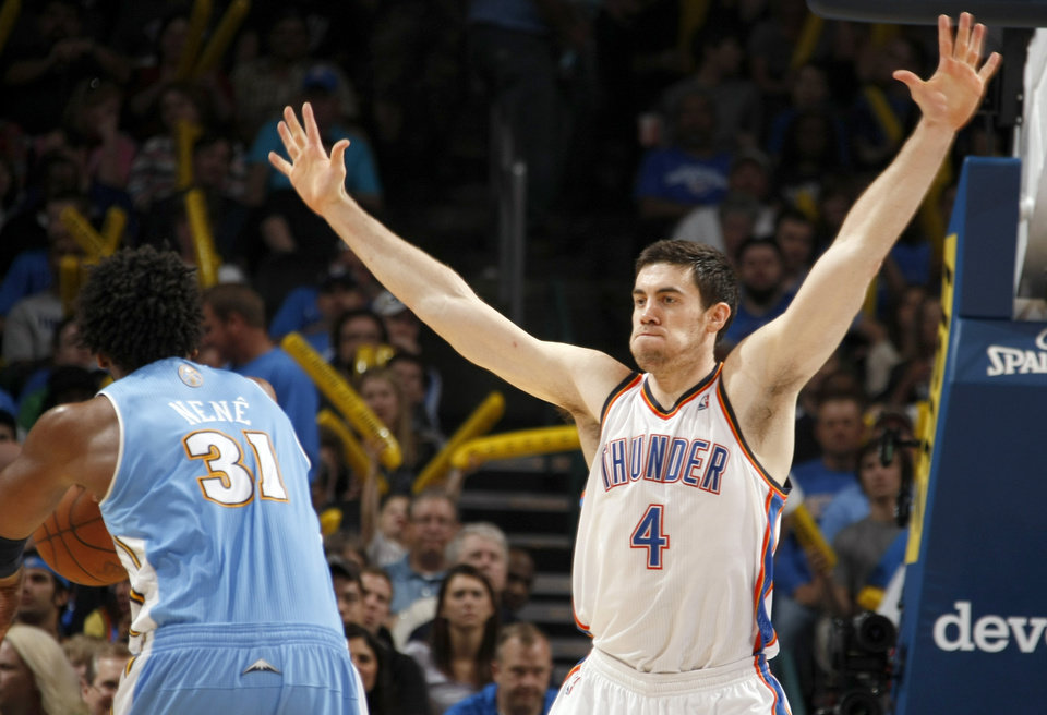 Photo - Oklahoma City's Nick Collison (4) defends Denver's Nene (31) during the NBA basketball game between the Oklahoma City Thunder and the Denver Nuggets, Friday, April 8, 2011, at the Oklahoma City Arena.. Photo by Sarah Phipps, The Oklahoman