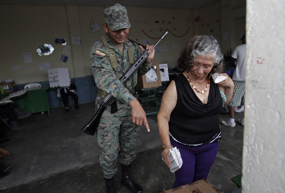 Photo - A soldier points the ballot box to a woman as she votes at a polling station in Quito, Ecuador, Sunday, Feb. 17,  2013. Ecuadoreans  elect president,  vice-president and National Assembly members Sunday with President Rafael Correa highly favored to win a second re-election.(AP Photo/Dolores Ochoa)