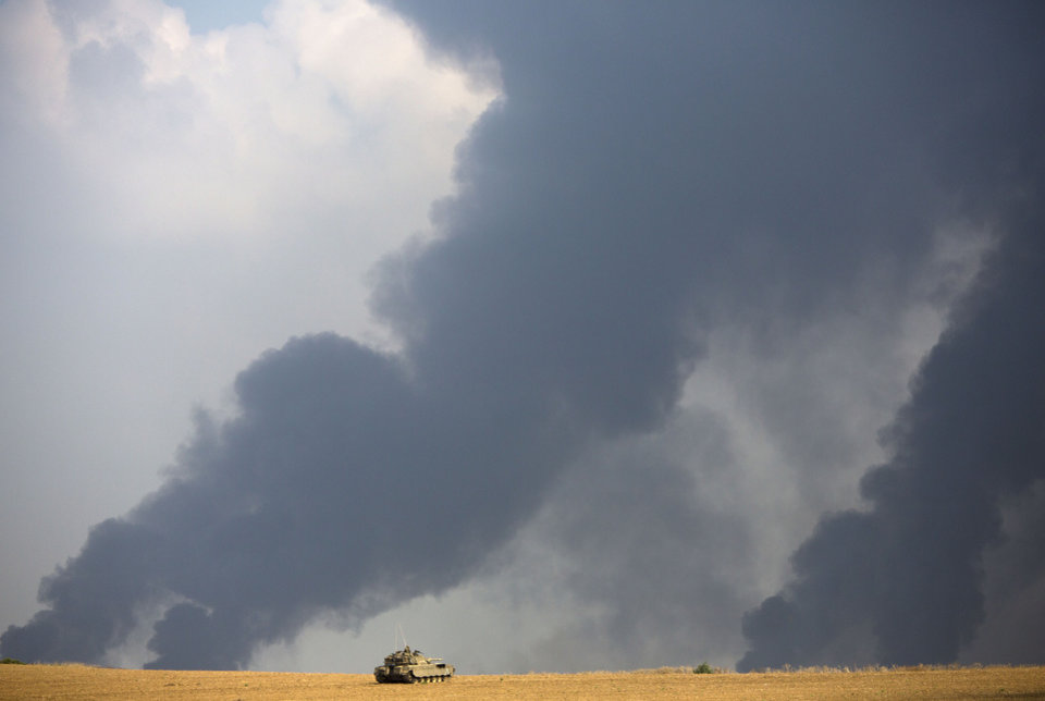 Photo - An Israeli tank sits in a field as heavy smoke rises from the Gaza Strip Tuesday, July 22, 2014. Israeli airstrikes pummeled a wide range of targets in the Gaza Strip on Tuesday as the U.N. chief and the U.S. secretary of state began an intensive effort to end more than two weeks of fighting that has killed hundreds of Palestinians and tens of Israelis. (AP Photo/Dusan Vranic)