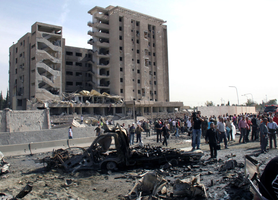 Photo - Syrian gather in front of a damaged military intelligence building where two bombs exploded, at Qazaz neighborhood in Damascus, Syria, on Thursday May 10, 2012. Two strong explosions ripped through the Syrian capital Thursday, killing or wounding dozens of people and leaving scenes of carnage in the streets in an assault against a center of government power. (AP Photo/Bassem Tellawi) ORG XMIT: BEI116