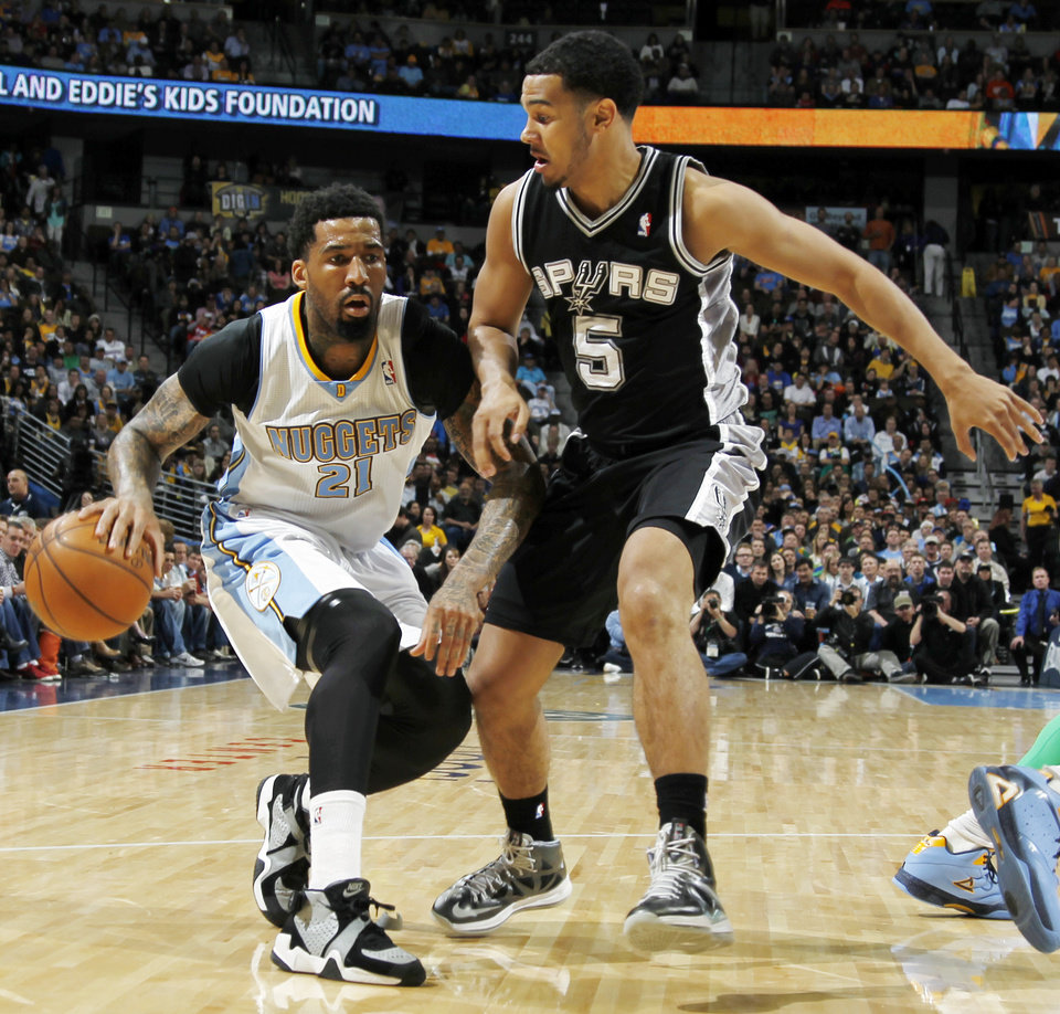 Denver Nuggets forward Wilson Chandler, left, drives against San Antonio Spurs guard Cory Joseph in the first quarter of an NBA basketball game in Denver, Wednesday, April 10, 2013. (AP Photo/David Zalubowski)