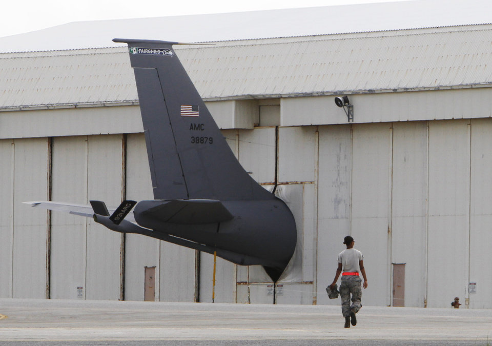 In this Aug. 14, 2012 photo, a ground crew member walks towards the tail of a U.S. Air Force KC-135 Stratotanker protruding from a hanger at Kadena Air Base on Japan's southwestern island of Okinawa. The most recent of the KC-135 refueling tankers currently in service started flying in 1964. For decades, the U.S. Air Force has grown accustomed to such superlatives as unrivaled and unbeatable. Now some of its key aircraft are being described with terms like decrepit. (AP Photo/Greg Baker)