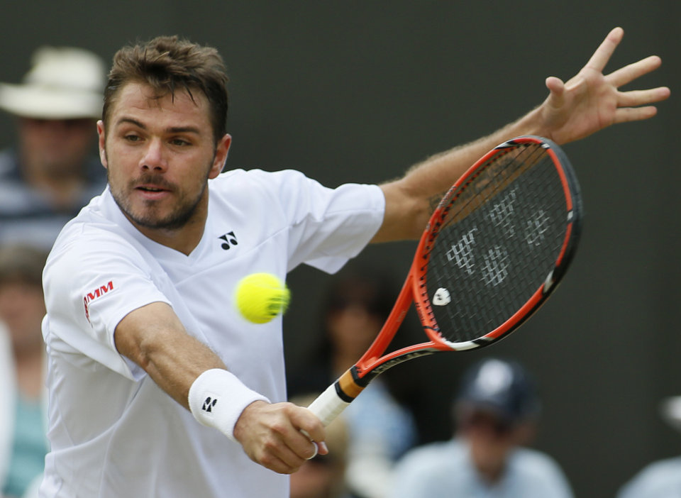 Photo - Stan Wawrinka of Switzerland plays a return to Denis Istomin of Uzbekistan during their men's singles match at the All England Lawn Tennis Championships in Wimbledon, London, Monday, June 30, 2014. (AP Photo/Alastair Grant)